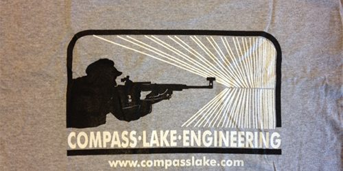 Gray Compass Lake Engineering t-shirt image of person holding rifle